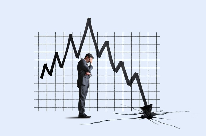 A businessman covers his eyes with a down stock chart in front of him.