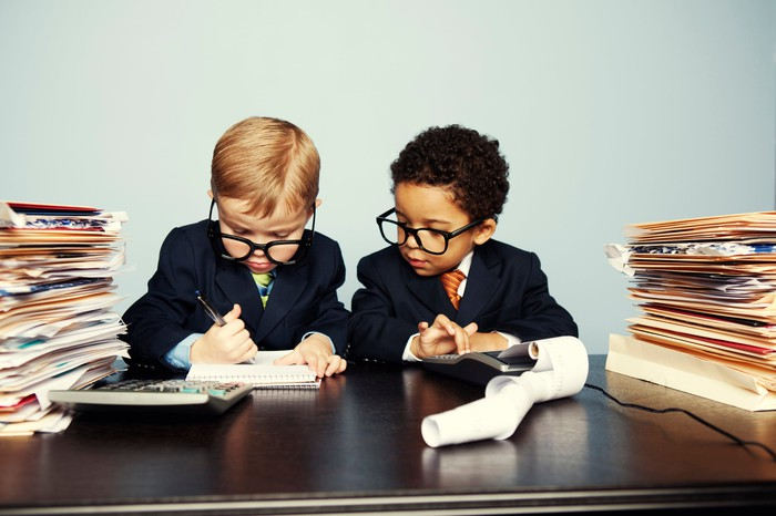 Two toddlers wearing business suits and oversized spectacles appear overwhelmed amid notebooks, a calculator, and stacks of documents in folders.