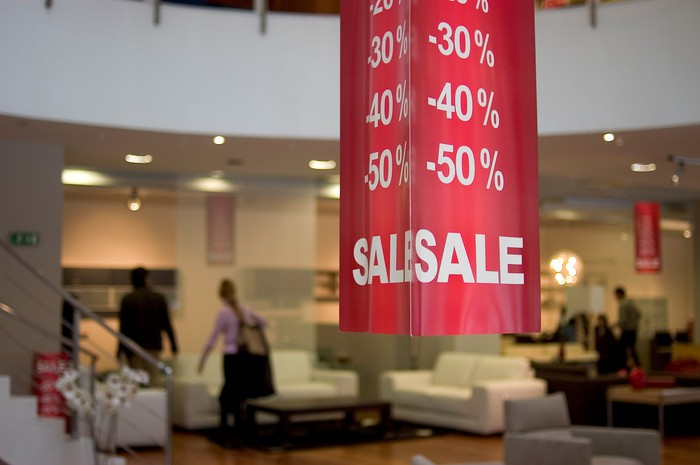 A furniture showroom with a 50% off sale banner.
