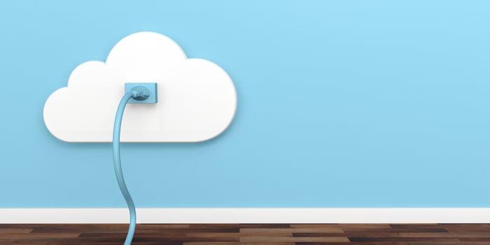 A blue network cord plugged into a cloud-shaped wall jack.