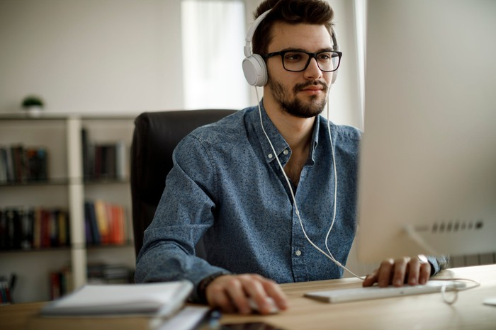 Man with headphones at desk on computer.
