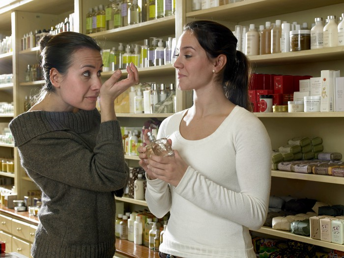 A customer testing out perfumes with the help of a sales clerk, in front of shelves holding perfumes and personal care products.