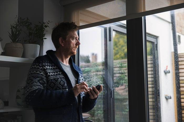 Un homme, tenant un téléphone, regardant par la fenêtre, représentant quelqu'un qui cherche à long terme.