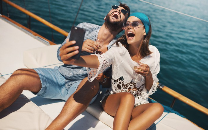 A couple takes a selfie on the deck of a ship.