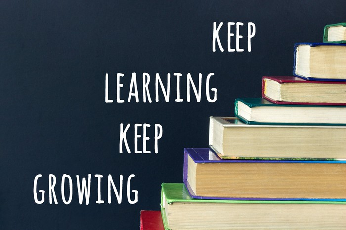 Next to a stack of books are the words keep learning keep growing.