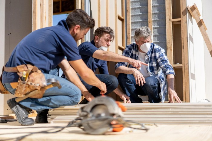 Three workers at a home construction site, with tools and a rotary saw.