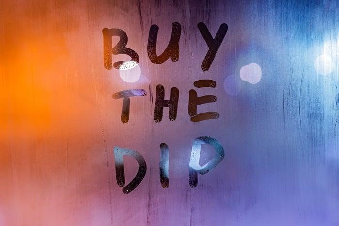"""""""Buy the dip"""" written on a foggy window."""