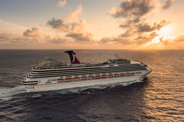 Carnival Sunshine cruise ship prowling the waves during sunset or sunrise.