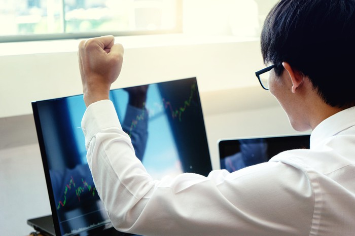 A person is celebrating while looking at a rising stock chart on a laptop computer.