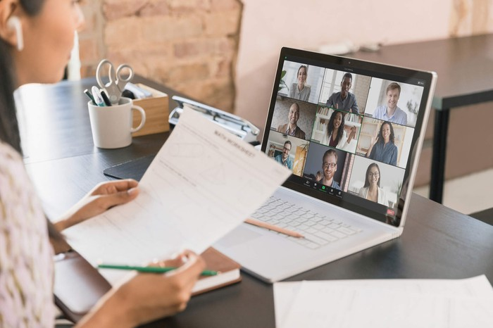 Woman at desk speaking with nine other people on Zoom