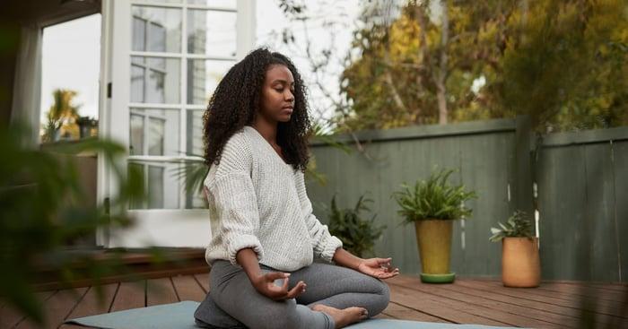 Personne assise sur un tapis à l'extérieur dans une pose de méditation.