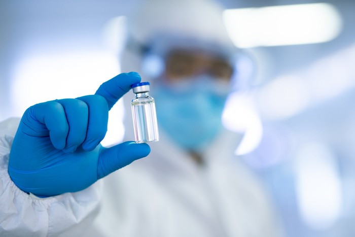 Masked doctor holds up vial of COVID-19 vaccine