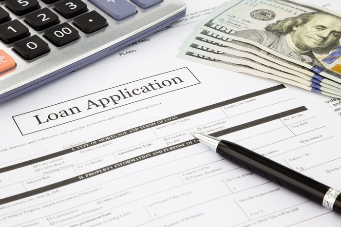 Paper marked loan application with cash, a pen, and a calculator.