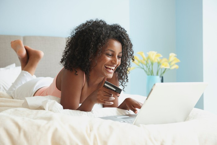 Smiling woman lying on a bed doing some online shopping.