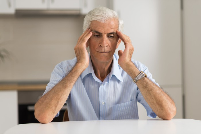 Older man holding his head as if stressed