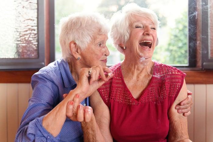 Two elderly women smoking marijuana and laughing.
