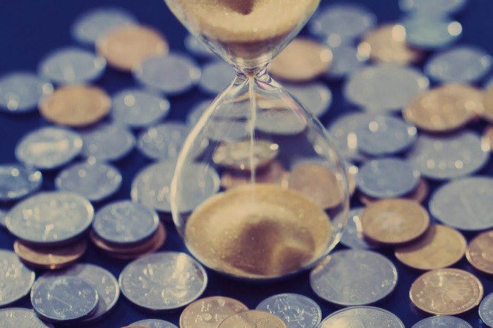 An hourglass stands in the middle of a large pile of coins.