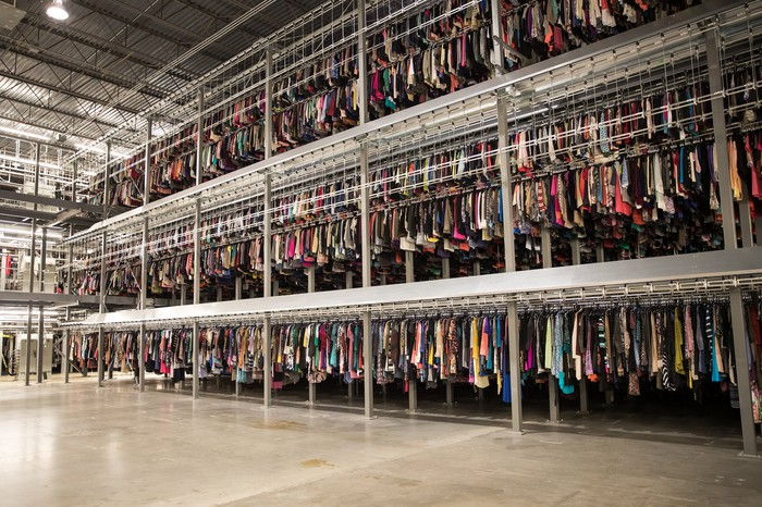 A ThredUP distribution center shows an extensive selection of clothes hanging up.
