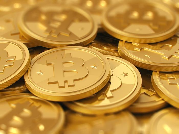 A pile of gold Bitcoin tokens.