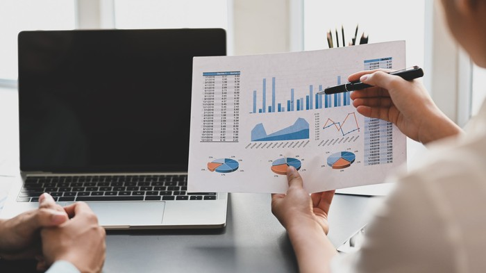 Examining a business chart in front of a laptop.