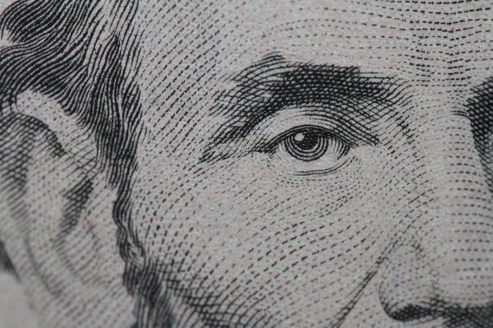 A close up of Abraham Lincoln's face on the $5 bill.
