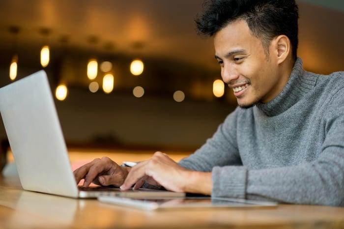 Um homem digitando em um laptop dentro de um café.