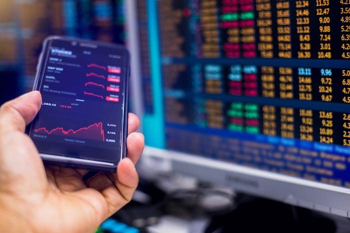 Uma pessoa segurando um smartphone exibindo cotações de ações ao lado de um monitor que mostra dados comerciais em tempo real.
