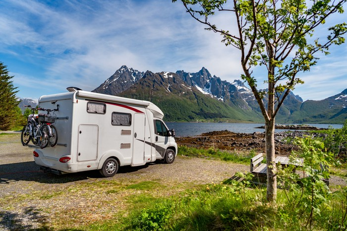 An RV parked near a lake with mountains on the opposite shore.