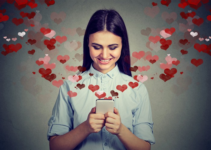 Hearts flowing from a phone held by a woman.