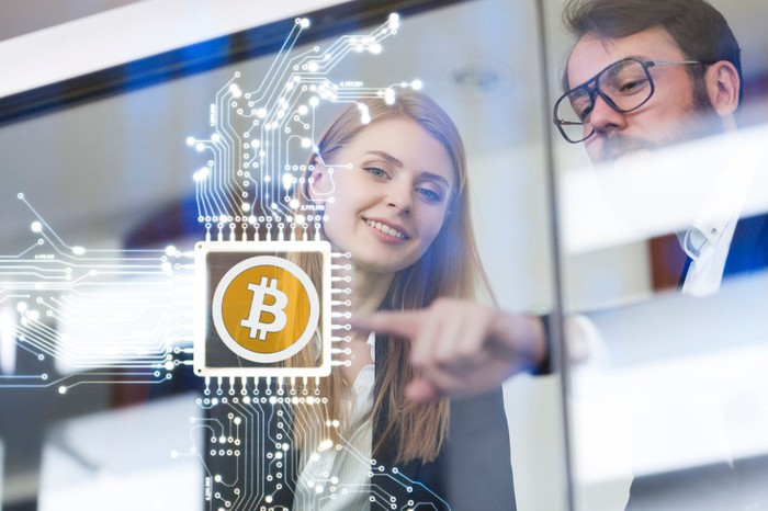 A woman and a man looking at a semiconductor chip with a Bitcoin logo hovering in the air.