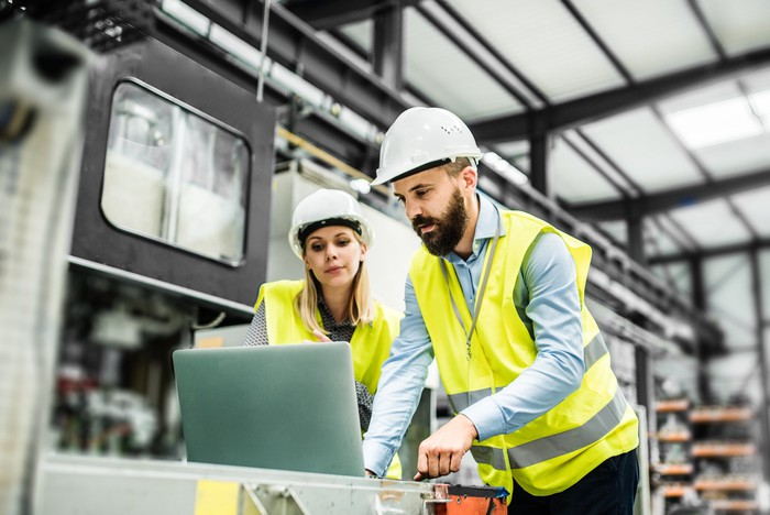 A man and woman in yellow vests and hard hats working in a factory setting.