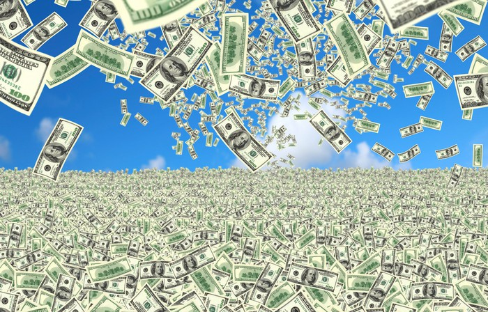 $100 bills falling from the sky into a field of money