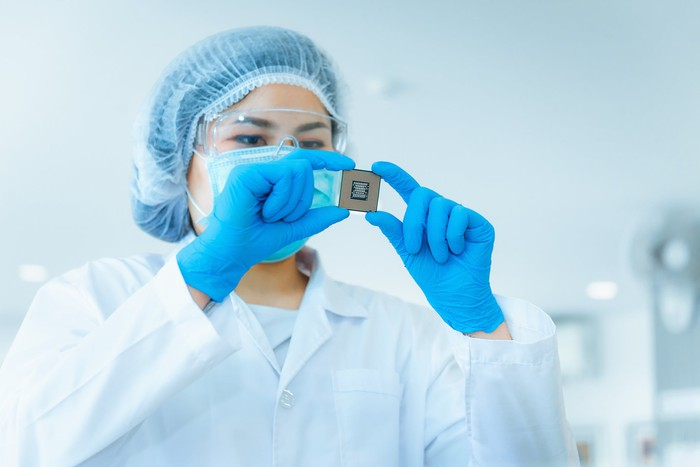 A worker examines a computer chip while wearing safety equipment in a lab setting