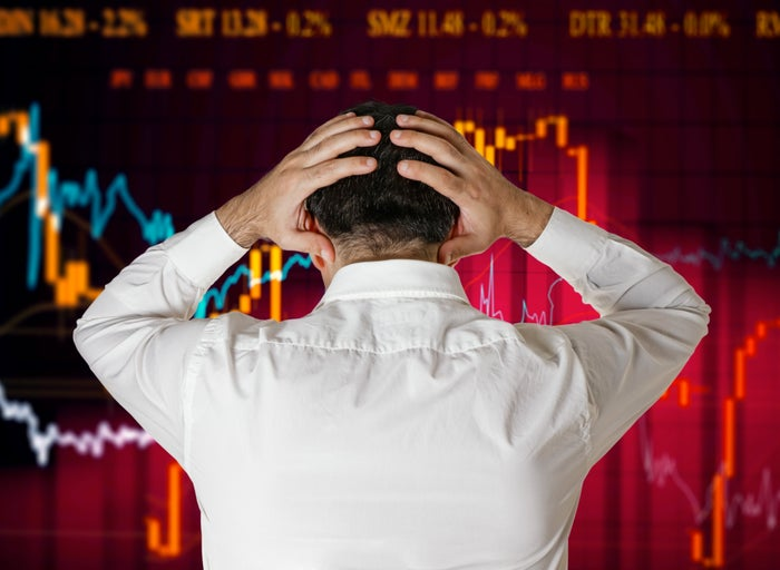 A businessman turns away from the camera to face a down red stock chart in the background.