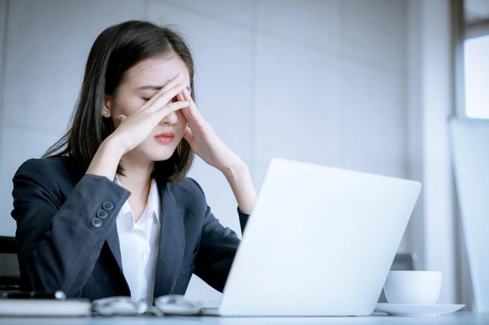 Woman with hands folded in front of her face and a worried look sits in front of an laptop.