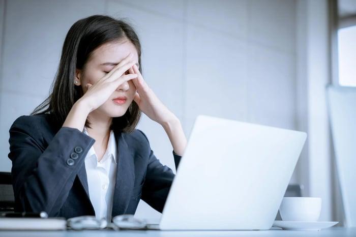 Femme avec les mains jointes devant son visage et un regard inquiet se trouve devant un ordinateur portable.