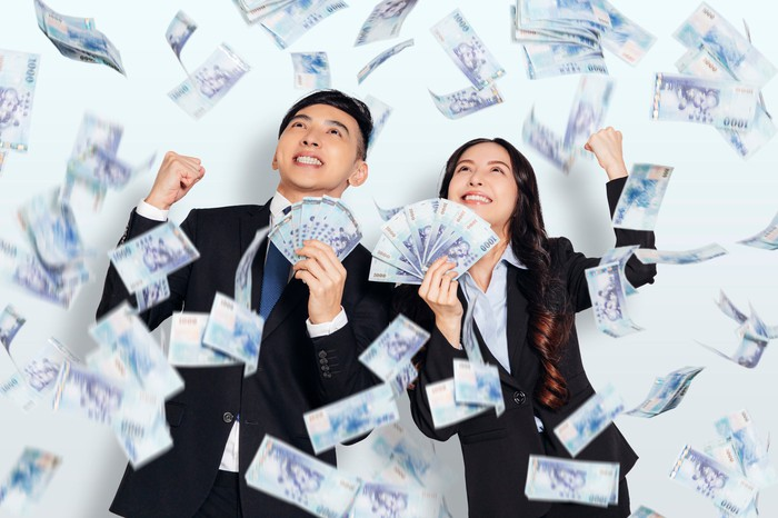 Two people in business suits with money flying around.
