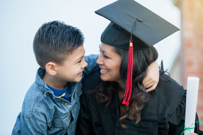 Proud child hugging mom in cap and gown.