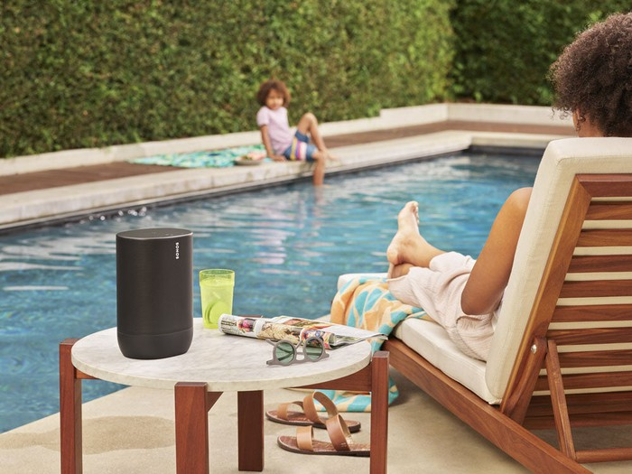 A person sits by a pool listening to a Sonos speaker.