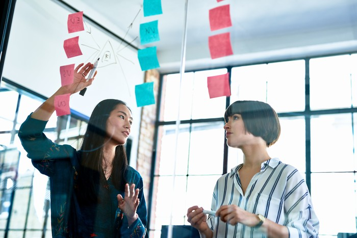 A businesswoman points to a series of sticky notes while talking with a coworker.