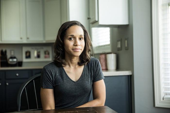 Une femme assise à sa table de cuisine à la recherche d'inquiétude ou d'inquiétude.