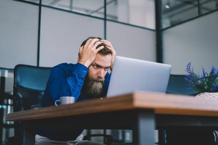 Homme tenant la tête tout en regardant un ordinateur portable