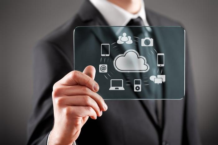Personne tenant une tablette claire représentant une icône de nuage entourée d'appareils photo, de tablettes, de smartphones, d'ordinateurs portables et de bulles de texte.