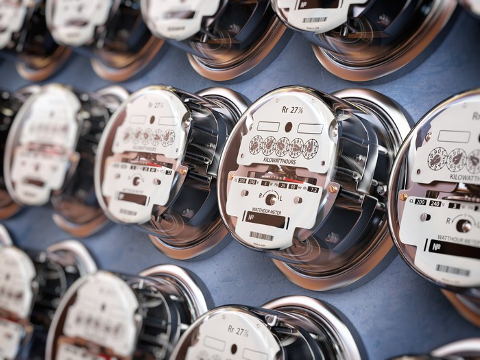 Multiple rows of electric meters on a panel.