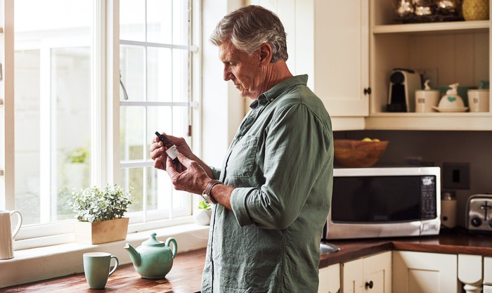 Mature person reads the label on a bottle of CBD oil while standing near a cup of tea in the kitchen.