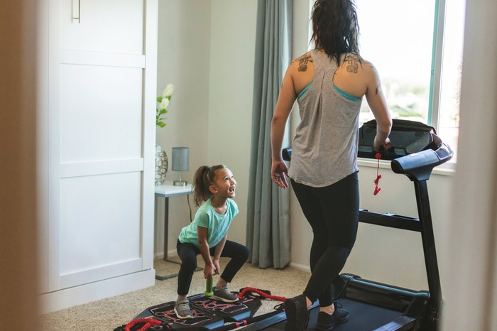 Child looking at lady using treadmill in house.