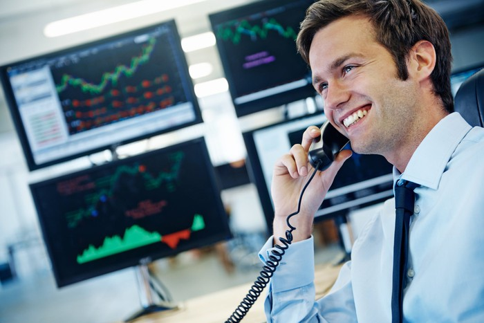 Smiling young man talking on phone while sitting in front of desktops displaying financial market information.