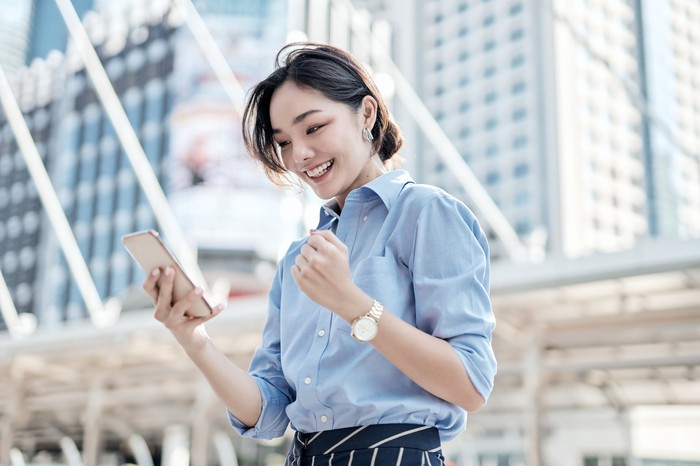 A young woman smiles at her phone and pumps her fist.