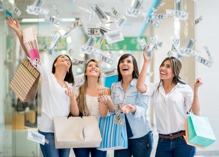 Quatre jeunes femmes attrapent des billets volants en faisant leurs courses.
