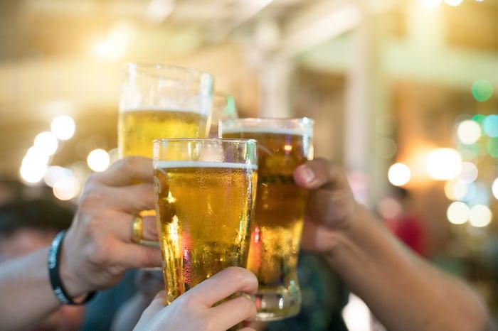 Three friends drink pint glasses of beer.